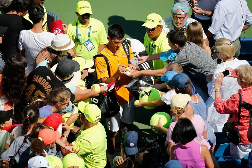 Djokovic signs autographs after defeating Alexandr Dolgopolo.