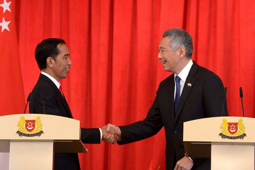 Indonesian President Joko Widodo (left) and Singapore Prime Minister Lee Hsien Loong shaking hands after a joint news conference at the Istana Presidential Palace in Singapore, on July 28, 2015.