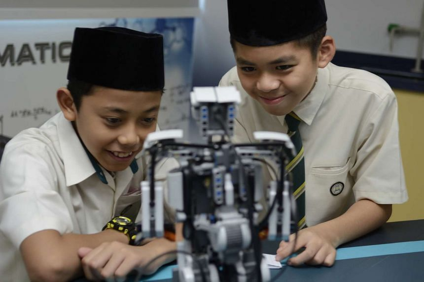 Pupils from Madrasah Irsyad Zuhri Al-Islamiah taking a close-up look at the equipment in the madrasah's STEM Lab during the laboratory's opening ceremony on Saturday, March 28, 2015.