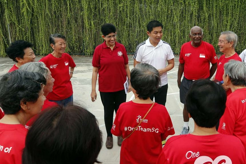 Minister for Social and Family Development Tan Chuan-Jin (in white) and with Marine Parade GRC MP Fatimah Lateef (centre) chatting with a group of elderly residents before visiting Tai Keng Gardens in Geylang Serai Division on Aug 23, 2015.