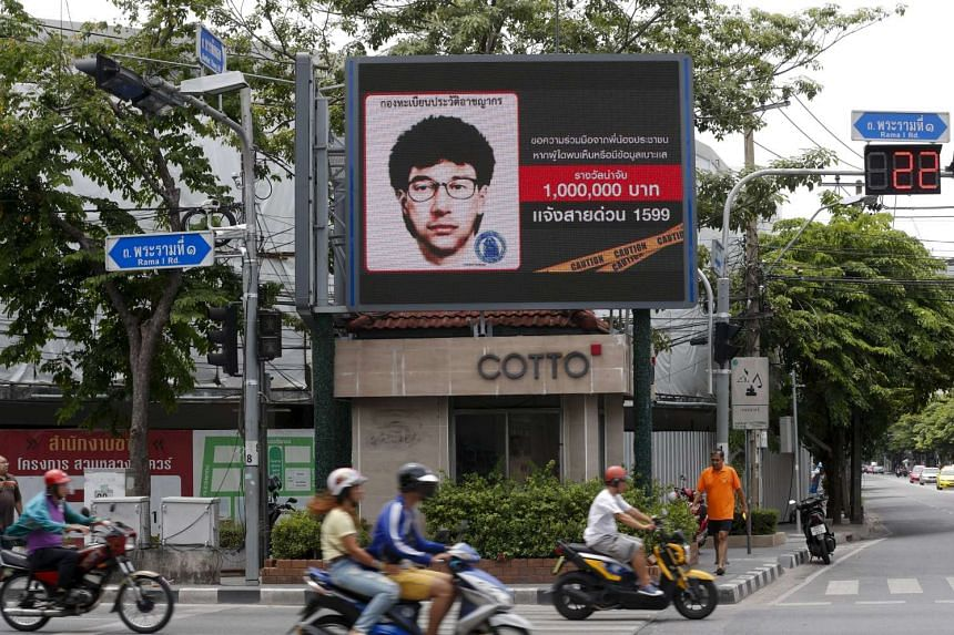 People ride their motorcycles past a digital billboard showing a sketch of the main suspect in Monday's attack on Erawan shrine, in Bangkok, Thailand, on Aug 23, 2015.