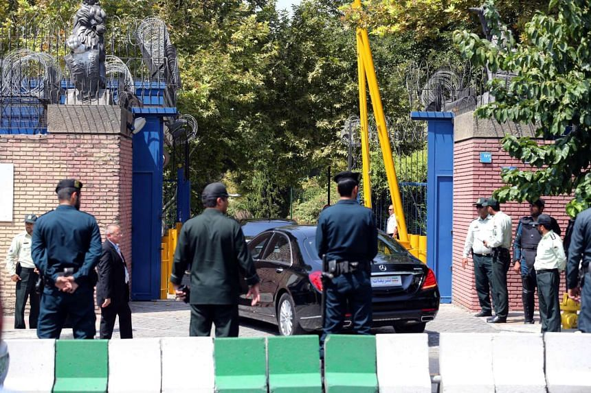 Iranian security forces stand guard as Britain's Foreign Secretary Philip Hammond arrives in his car at the British embassy on Aug 23, 2015, in the capital Teheran.
