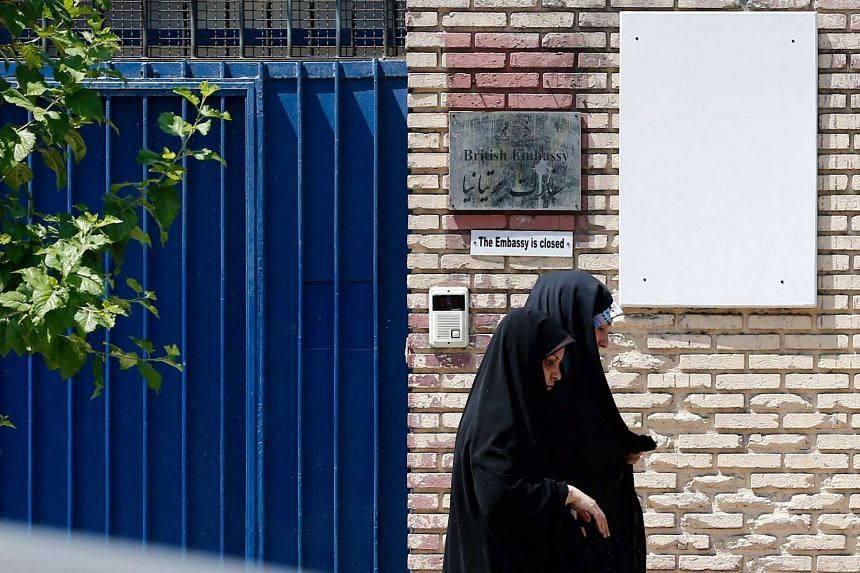 Iranian women walk in front of the closed British embassy in Teheran, Iran, on Aug 21, 2015.