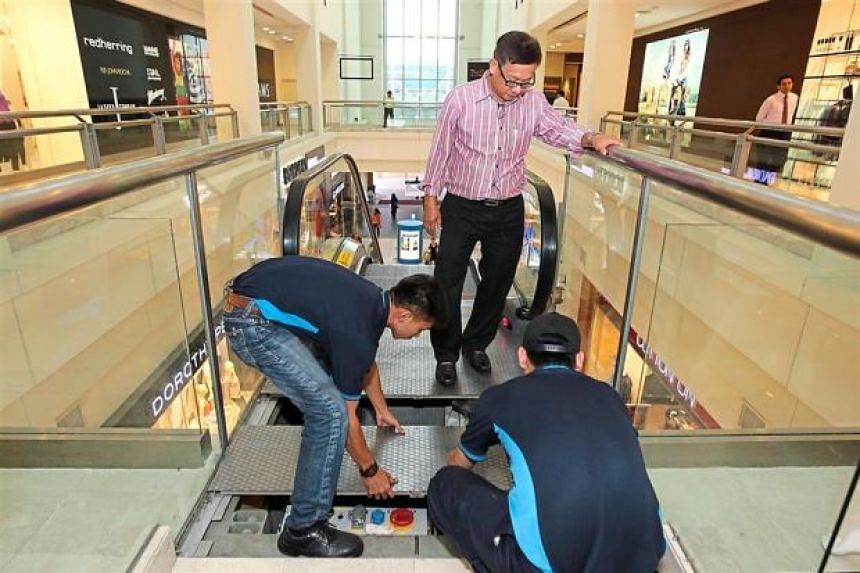 Workers checking on an escalator in a Malaysian shopping mall.