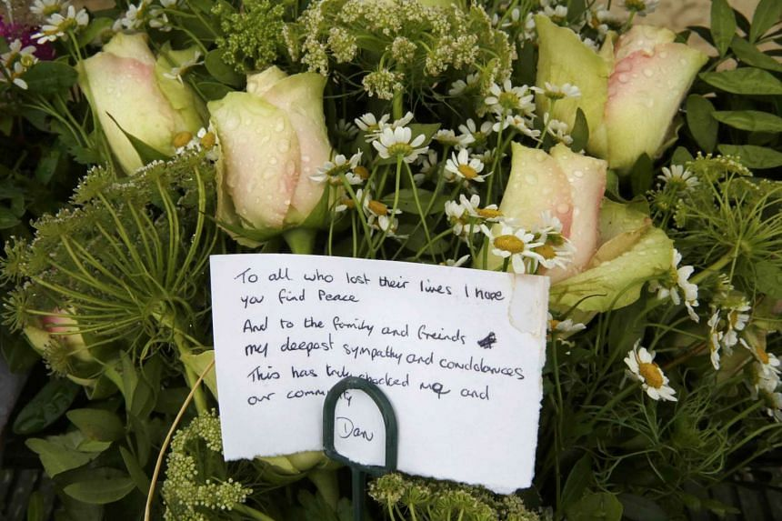 :A message is seen on a floral tribute left near the site where a Hawker Hunter fighter jet crashed onto the A27 road at Shoreham near Brighton during  an airshow in southern England on Saturday.