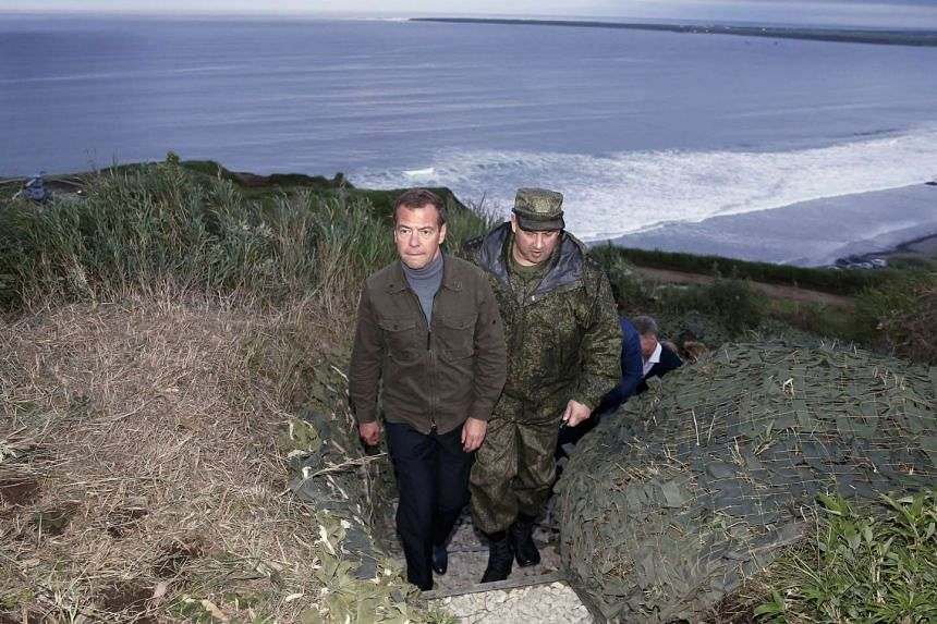 Dmitry Medvedev (left) visits a machine gun regiment on Iturup island, one of four islands in the chain that lies off Russia's far eastern coast and just north of Japan, on Aug 22, 2015.