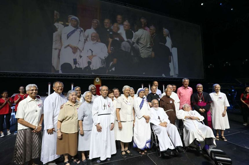 Prime Minister Lee Hsien Loong (in pink) posing with members of the Roman Catholic community during a special Mass said to celebrate SG50.