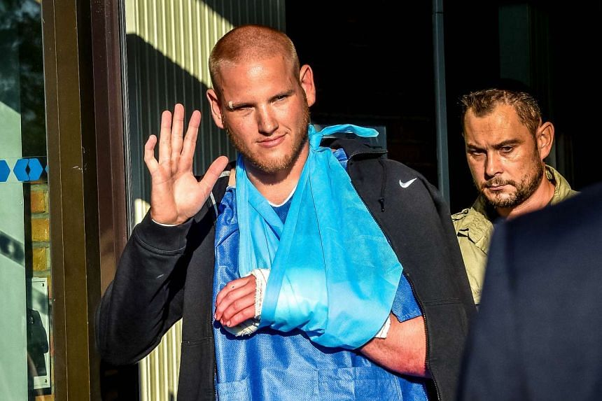 Spencer Stone (left) gestures as he leaves hospital in Lesquin, northern France.