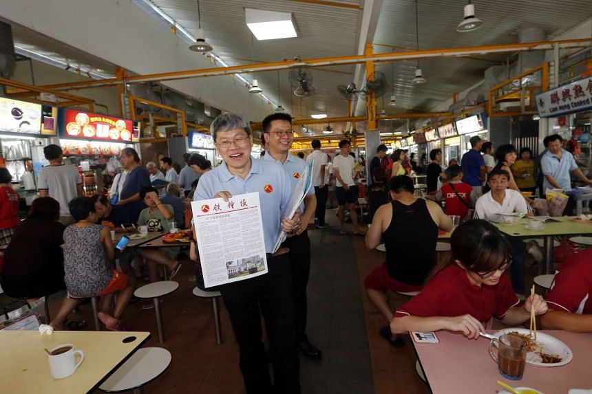 Mr Png Eng Huat (holding sign) and Mr Daniel Goh of the Workers' Party at the Fengshan hawker centre earlier this month.