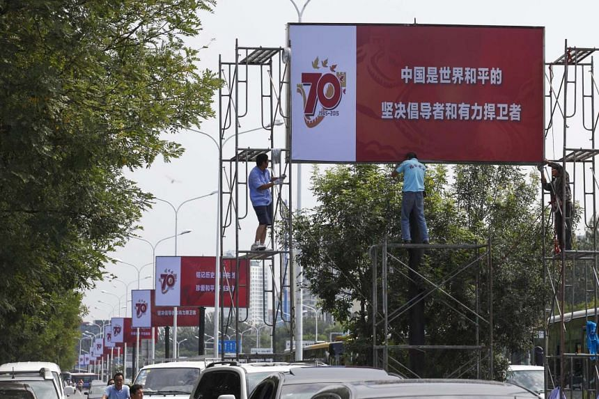 Chinese workers installing banners for the 70th anniversary of the end of World War II in Beijing on Aug 23, 2015.
