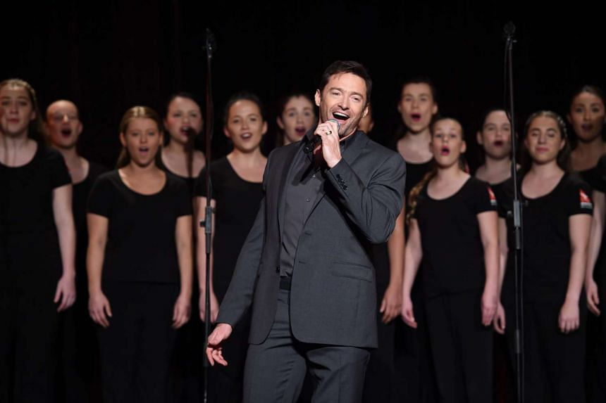 Hugh Jackman sings with the Qantas choir during a media conference in Sydney on Aug 24, 2015.
