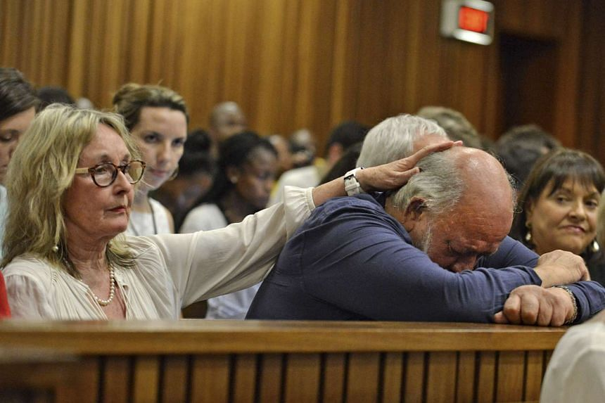 Barry Steenkamp, father of Reeva Steenkamp, is consoled by his wife June Steenkamp during the sentencing hearing of Olympic and Paralympic track star Oscar Pistorius at the North Gauteng High Court in Pretoria in this Oct 15, 2014, file photo.
