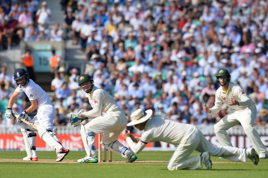 Adam Lyth (left) looks over as Australia's Michael Clarke (2nd right) picks up the ball on the second day of the fifth Ashes cricket Test match between England and Australia at the Oval in London on Aug 21, 2015.