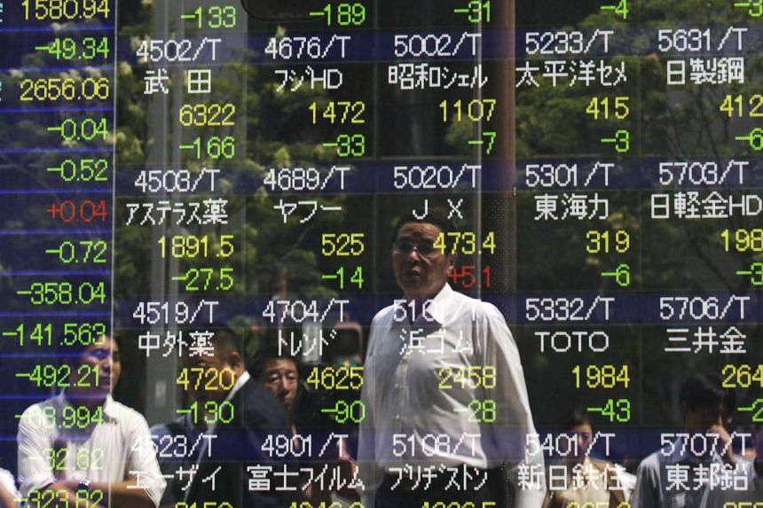 A businessman is watching the Tokyo stock index in the morning trade session on a display in Tokyo, Japan on Aug 21, 2015.