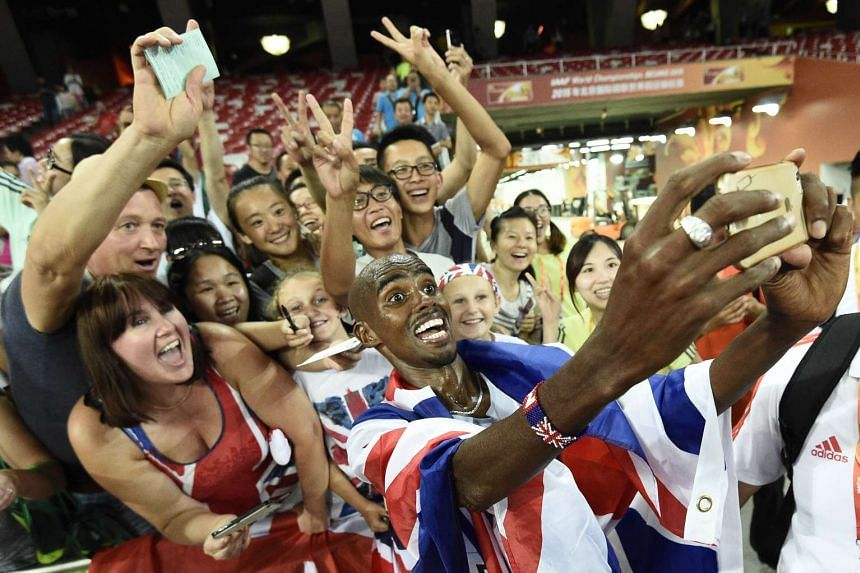 Mo Farah poses for 'selfies' with supporters after winning the final of the men's 10,000 metres athletics event at the 2015 IAAF World Championships in Beijing on Aug 22, 2015.