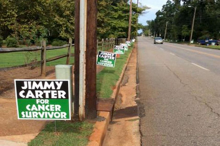 Lawn signs along a sidewalk is shown in this photo taken by former US President Jimmy Carter in Plains, Georgia.