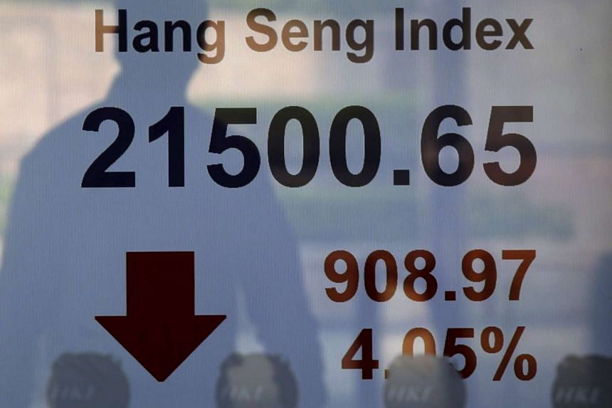 A passerby is reflected on a panel displaying the Hang Seng Index, which drops more than four per cent, at the Hong Kong Stocks Exchange in Hong Kong, China on Aug 24, 2015.