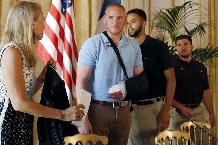 (From left) US ambassador to France Jane Hartley presents US Airman First Class Spencer Stone, student Anthony Sadler and National Guardsman Alek Skarlatos as they attend a ceremony at the US Embassy in Paris, France, Aug 23, 2015.
