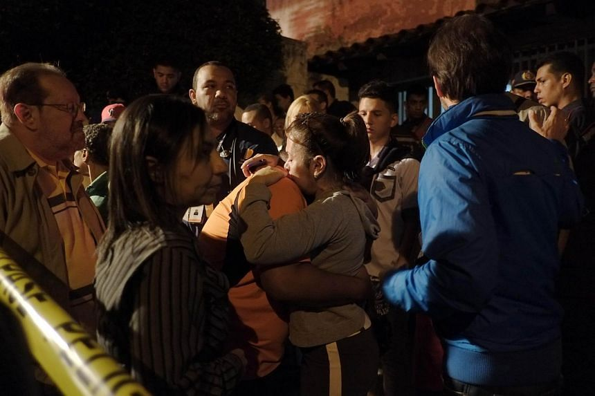 Relatives embrace after a fire at an old people's home in Caracas on Aug  23, 2015.