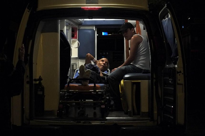 An elderly man is helped after a fire at an old people's home in Caracas on Aug 23, 2015.