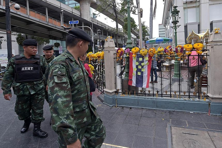 Thai soldiers patrolling the Erawan Shrine in Bangkok yesterday. Last Monday's bomb blast killed 20 people, including a Singaporean.