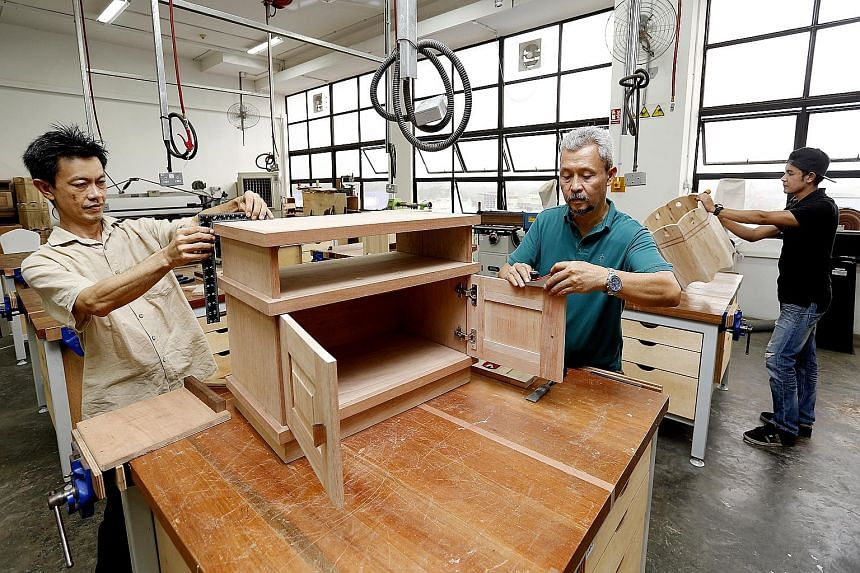 Under the new scheme, skilled foreign craftsmen can be recruited to train locals such as (from left) Mr Chen Teck Wah, Mr Sulaiman Suib and Mr Muhammad Iszad Razali, who graduated last year from a furniture craftsman programme.