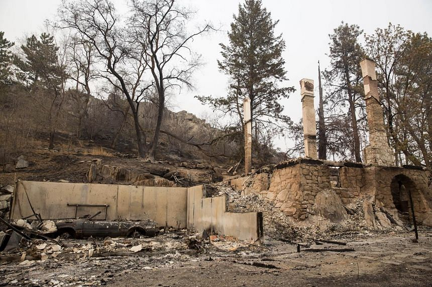 A charred car sits amid the ruins of a house destroyed by wildfires on Saturday near Okanogan, Washington. A series of blazes called the Okanogan Complex, which is made up of five wildfires in north-central Washington state, has scorched 65,154ha of