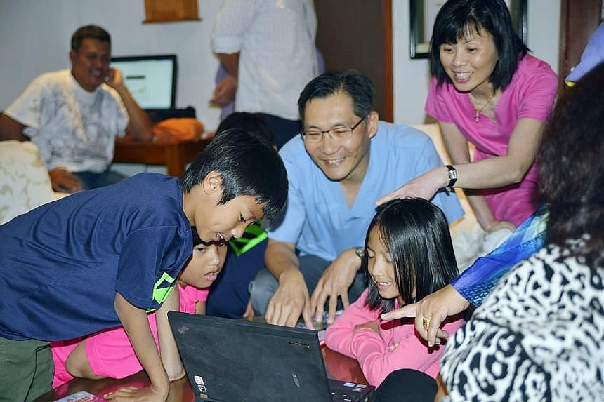 (Above, from left) Indonesian triplets Aisya Anjani, Aditya Harimurti and Artha Pradipta, nine, with younger sister Adinda Rania, seven. (Left) The children looking at family photos with Dr Cheng Li Chang (in blue shirt) and one of the nurses who att