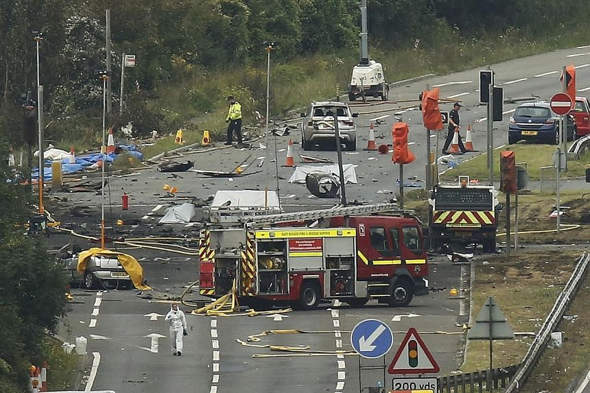 Emergency services and crash investigation officers working yesterday at the site where a Hawker Hunter fighter jet crashed onto the A27 road at Shoreham-by-Sea, a small seaside town and port in West Sussex, England. The aircraft ploughed into severa