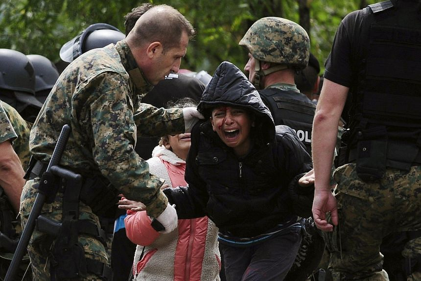 A migrant girl crying in relief after crossing Greece into Macedonia near Gevgelija last Saturday. After a futile attempt to slow down the flow of migrants, Macedonia laid on extra trains and buses to help ferry the migrants to Serbia instead.