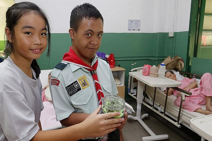 Swiss Cottage Secondary School student Amelie Chan Su Ying, 13 (left), and Minds student Amirul Hidyat, 15, with a terrarium that they made for residents of an old folks' home.