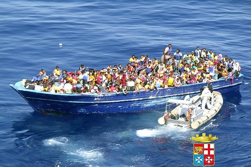 An image released by the Italian navy shows a boat crowded with refugees off the Italian coast last Saturday.