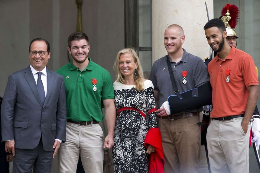 (From left) French President Francois Hollande, off-duty serviceman Alek Skarlatos, US ambassador to France Jane Hartley, off-duty serviceman Spencer Stone and off-duty serviceman Anthony Sadler pose for a picture on Aug 24, 2015 after a reception at