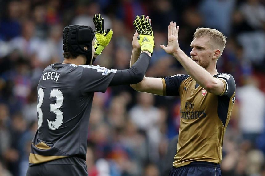 Arsenal's goalkeeper Petr Cech (left) and defender Per Mertesacker celebrate their win against Crystal Palace on Aug 16, 2015.
