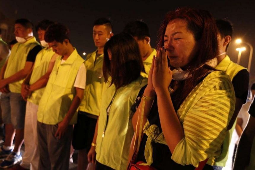 Local people pray for victims as they lay the flowers and light candles outside the Taida hospital after a huge explosion rocked the port city of Tianjin, China, on Aug 15, 2015.