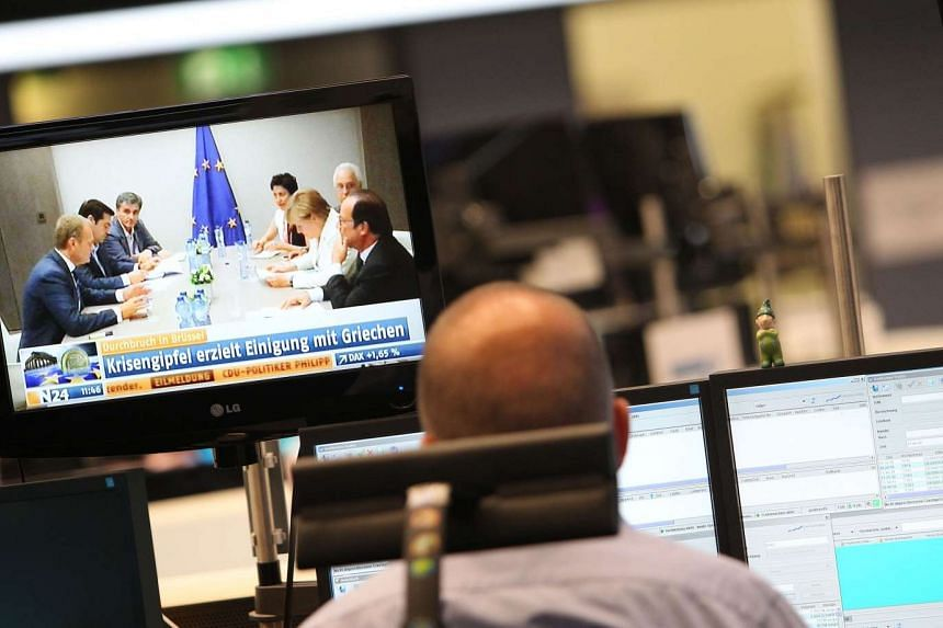 A trader works as one of his screens displays news on the Greek debt crisis at the stock exchange in Frankfurt am Main, western Germany, on July 13, 2015.