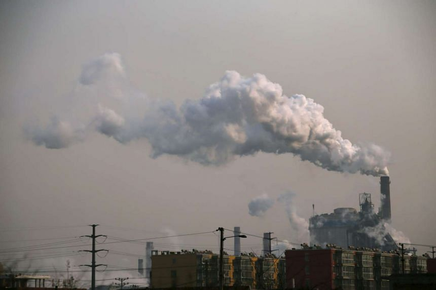 Smoke rises from a chimney of a steel plant next to residential buildings on a hazy day in Hebei.