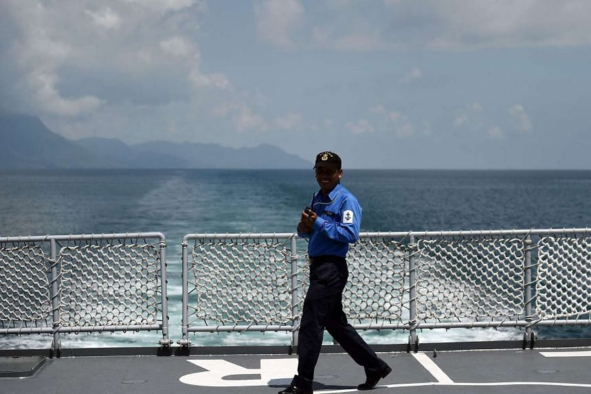 A Royal Malaysian Navy sailor walks on the deck of their ship.