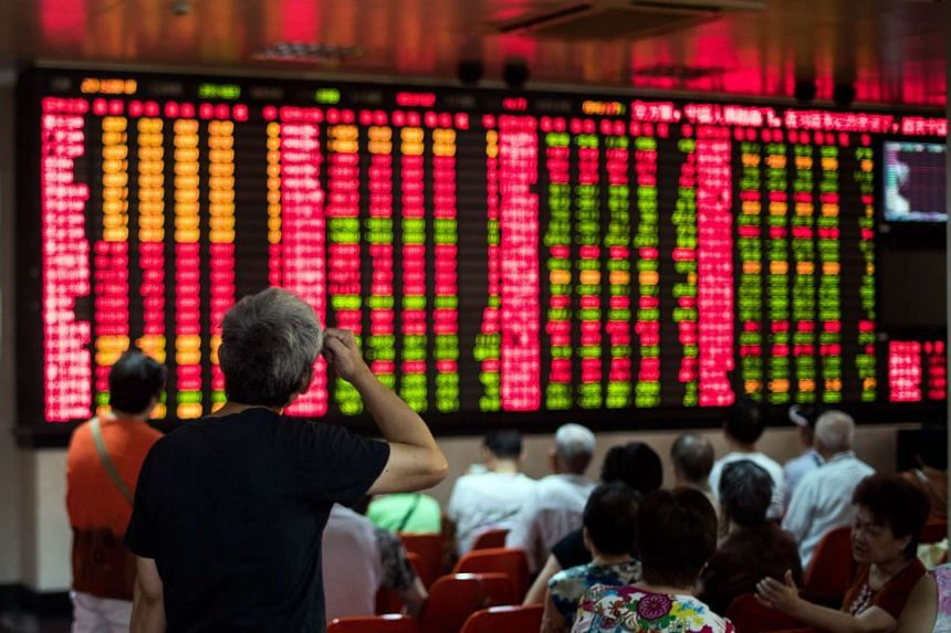 Investors monitoring screens showing stock market movements at a brokerage house in Shanghai.