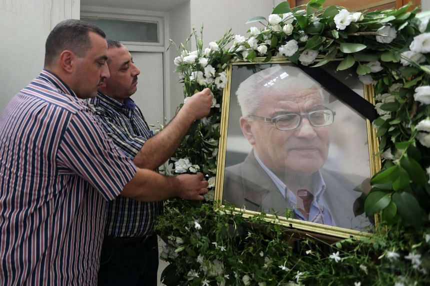 The sons of Khaled al-Assaad, the late 82-year old retired chief archaeologist of the ancient Syrian city of Palmyra, Omar (left) and Mohamad display a portrait of their father during a ceremony in his memory at the National Museum on Sunday in the S