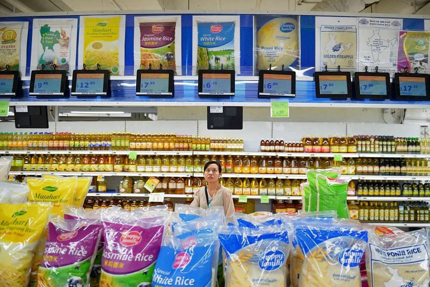 A woman looking at the price of rice at a supermarket.