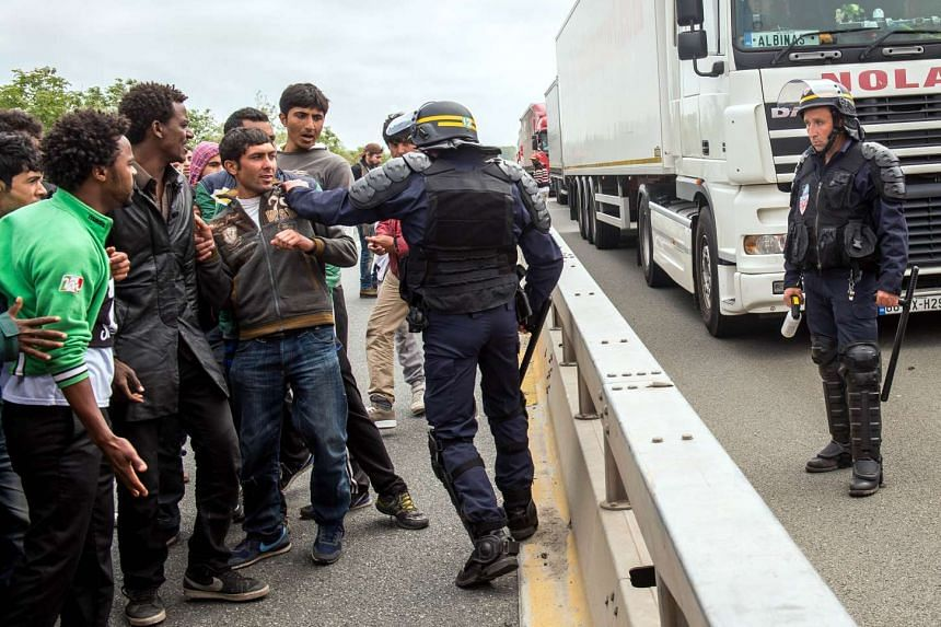 A French riot police officer pushes back a man as illegal migrants wait to attempt to hide in lorries heading for England, in the French northern harbour of Calais.