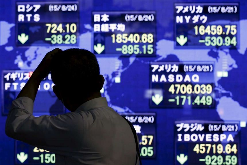 A man looking at market indices at a stock quotation board outside a brokerage in Tokyo, on Aug 24, 2015.