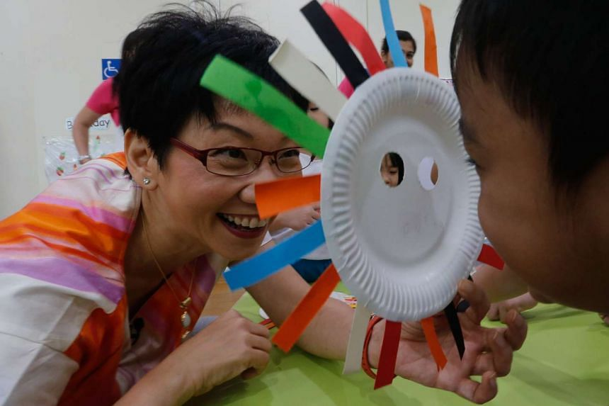 Second Minister for Foreign Affairs Grace Fu plays with a kindergartner and his handmade mask - she was at MY World Preschool @ Compassvale Ancilla Blk 281B, Sengkang East Avenue,  to give more details on measures to boost marriage and birth rates.