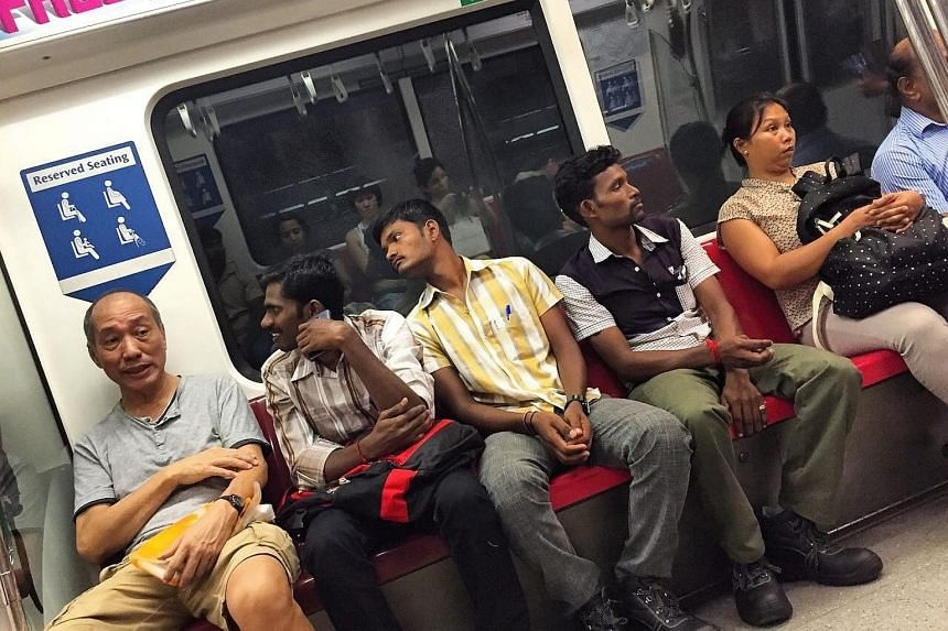 """Mr Sarvanan breaks into a smile after Mr Lau tells him """"Hey you can sit down... You don't always have to give up your seat, especially not to men on the train. You come here to build our homes so you can sit also you know?"""""""