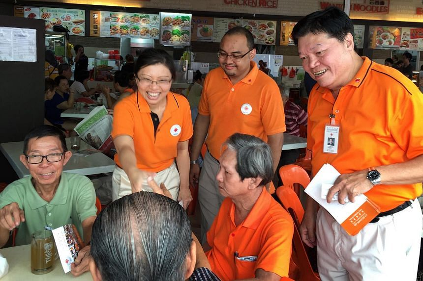 Ms Hazel Poa (left) shaking hands with a resident, during a walkabout with NSP's new face Mohamed Fazli Talip and chairman Sebastian Teo (right).