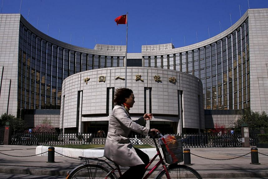 A woman riding past the headquarters of the People's Bank of China, the Chinese central bank, in Beijing.