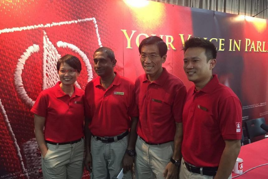 SDP party treasurer Chong Wai Fung (left) and accounts manager Khung Wai Yeen (right). With them is party chief Chee Soon Juan (second from right) and chairman Jeffrey George.