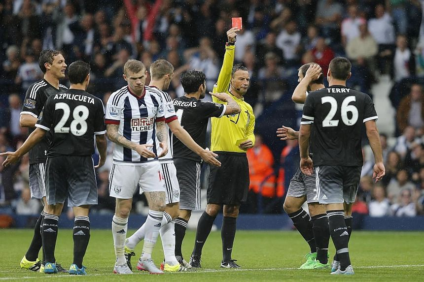 Referee Mark Clattenburg shows Chelsea captain John Terry a red card in the game against West Bromwich Albion on Sunday.