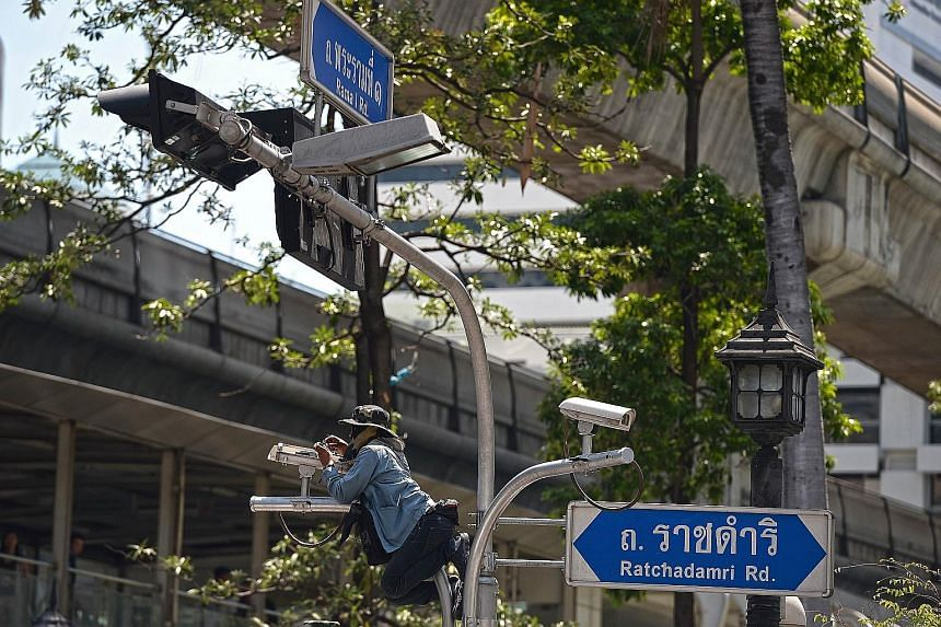 A worker last Thursday fixing a CCTV camera installed above the reopened Erawan Shrine, where 20 people were killed on Aug 17 in a bomb blast. National police chief Somyot Pumpanmuang has claimed that malfunctioning equipment was hampering investigat